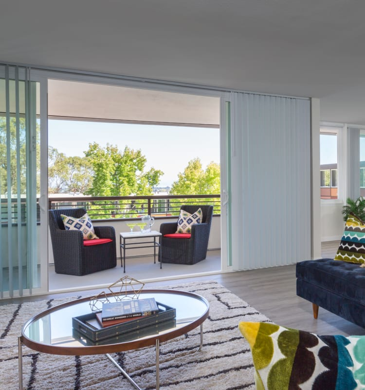 View of the well-decorated private balcony outside a model home's living room at Sofi Belmont Glen in Belmont, California
