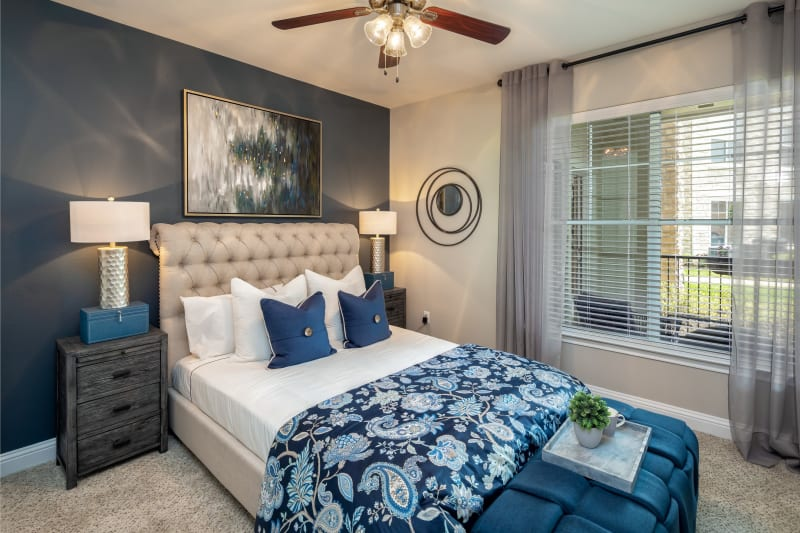 Well lit model bedroom with huge windows and a ceiling fan to cool you down at The Retreat at Cinco Ranch in Katy, Texas