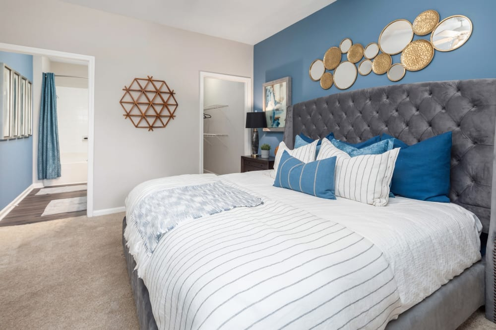 Beautifully furnished resident bedroom with a large cozy looking bed at Highlands at Alexander Pointe in Charlotte, North Carolina