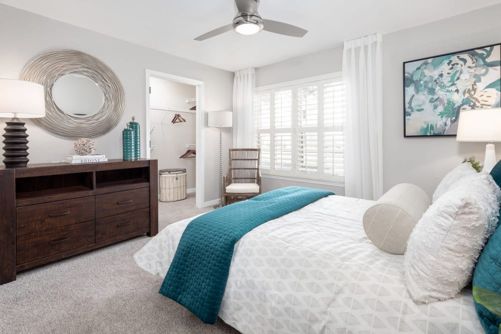 Model home's primary bedroom with a ceiling fan and plush carpeting at Amira at Westly in Tampa, Florida