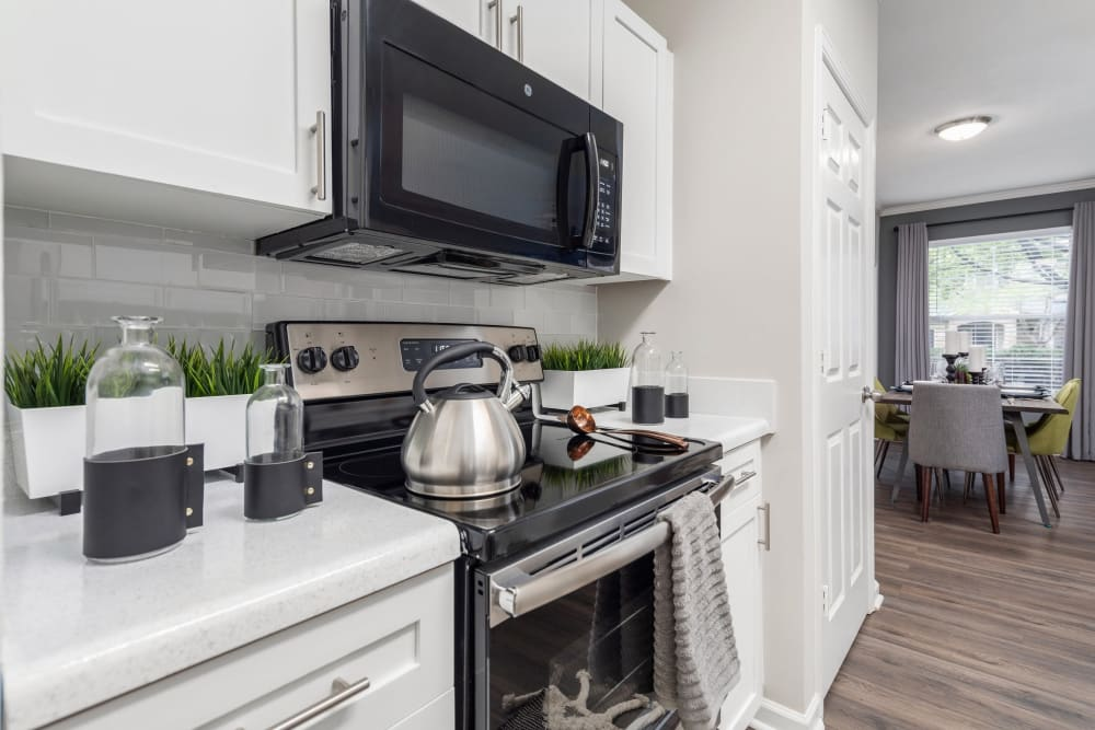 Model home's kitchen with modern stainless-steel appliances and white cabinetry at Highlands at Alexander Pointe in Charlotte, North Carolina