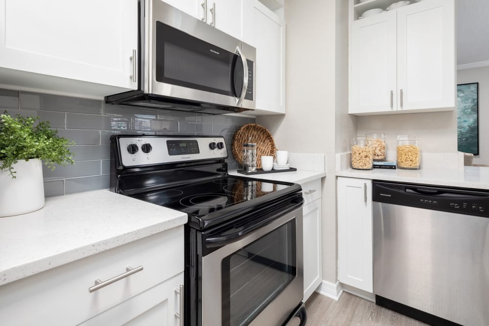 Stainless-steel appliances and white cabinetry in a model home's kitchen at Amira at Westly in Tampa, Florida