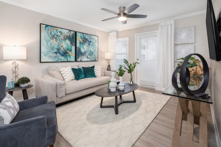 Well-furnished model home's living area with a ceiling fan at Amira at Westly in Tampa, Florida