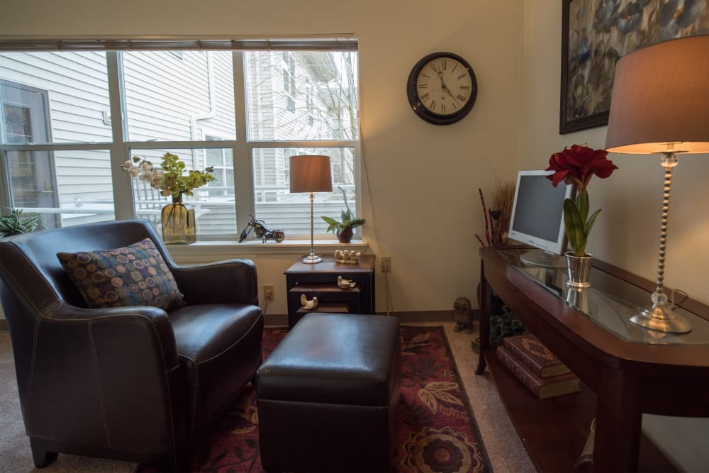 Resident living room with large window and leather furniture at Kenmore Senior Living in Kenmore, Washington