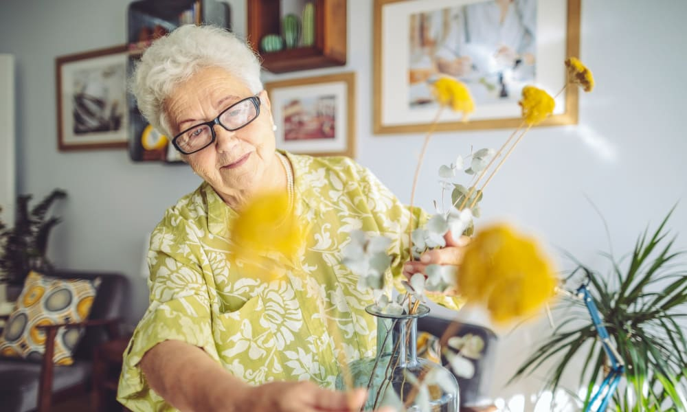 Resident arranging flowers in a vase at Randall Residence of Fremont in Fremont, Ohio