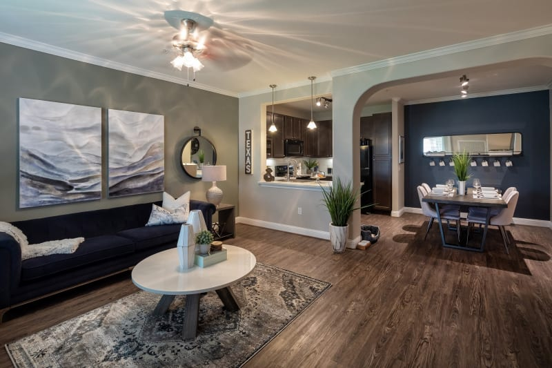 Living room with modern decor and gorgeous dark wood style flooring at The Retreat at Cinco Ranch in Katy, Texas