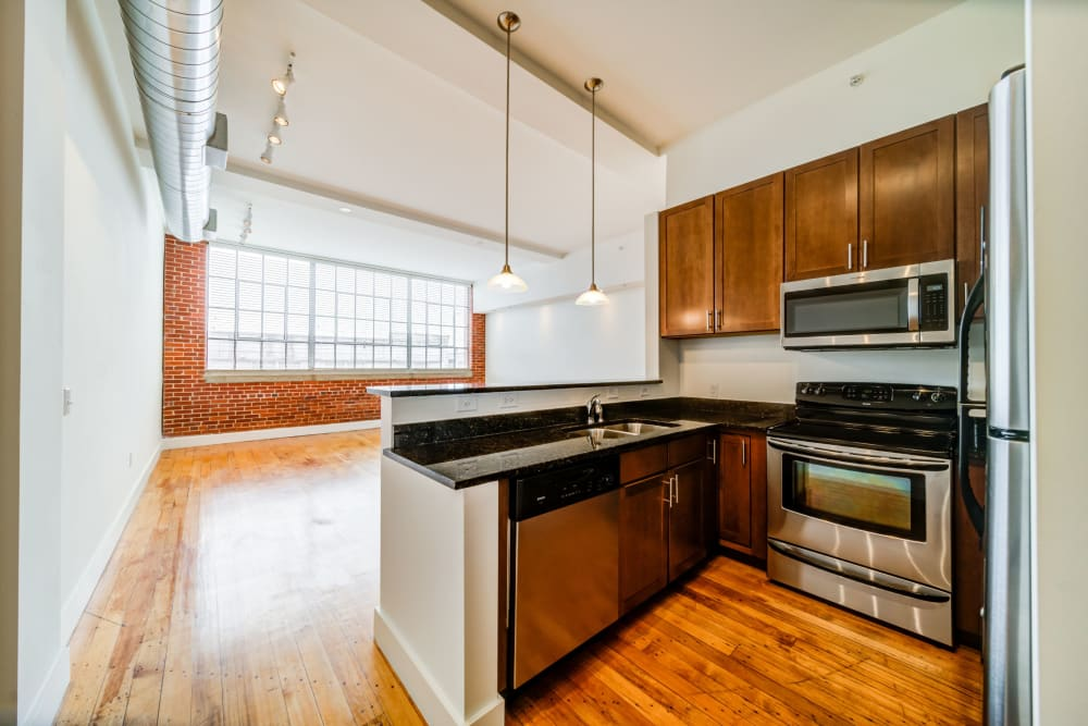 Kitchen with exposed brick and large windows at The Gallery Lofts in Winston Salem, North Carolina