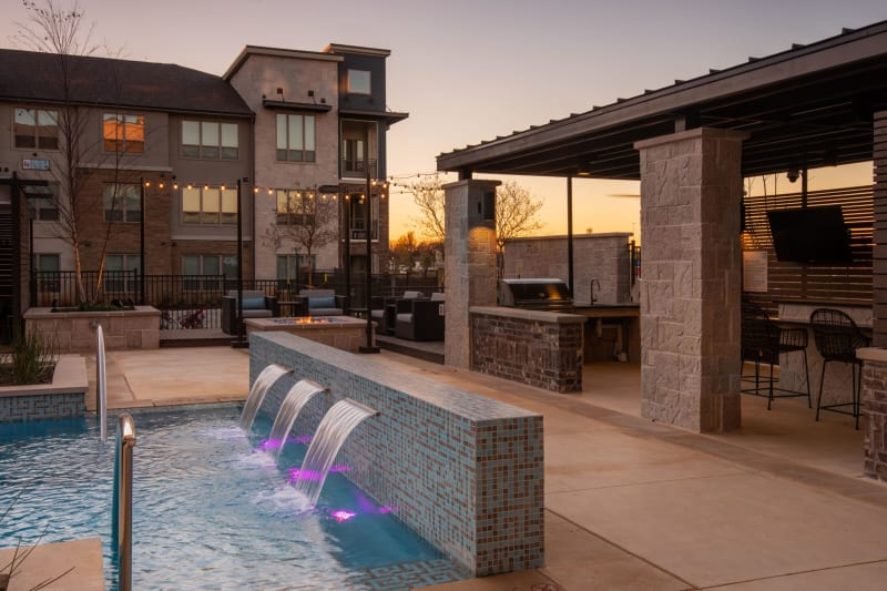 Outdoor pool area with seating and places to entertain poolside at Domain at Founders Parc in Euless, Texas