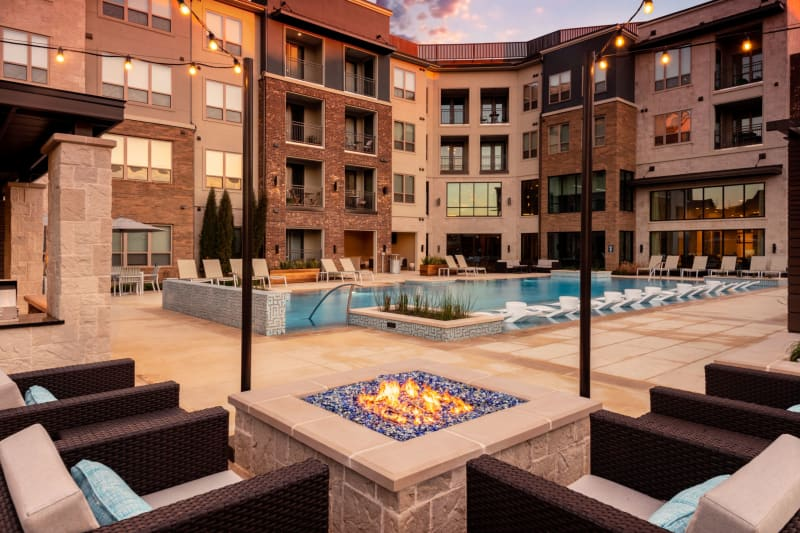 Outdoor fire area with seating and places to cook poolside at Domain at Founders Parc in Euless, Texas