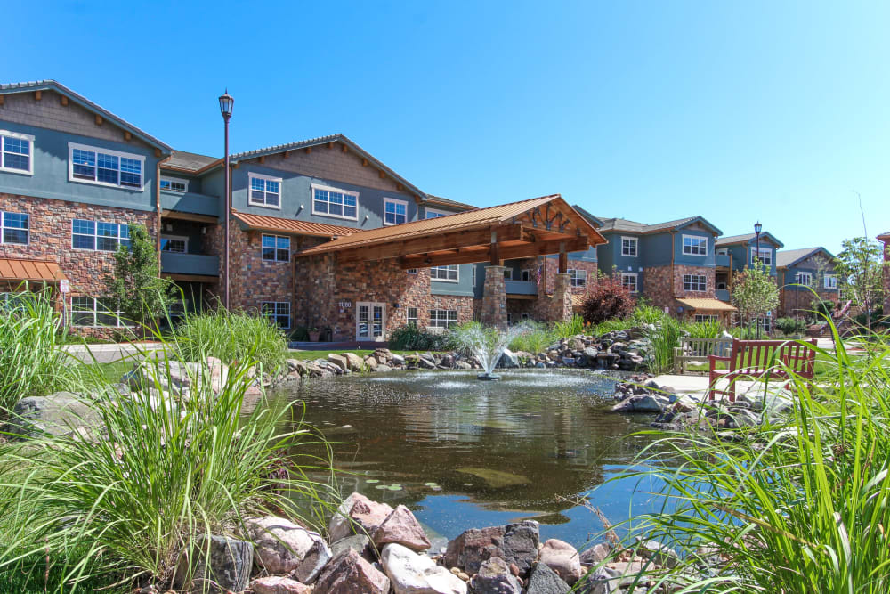 Grounds with walking paths and a pond at Keystone Place at Legacy Ridge in Westminster, Colorado