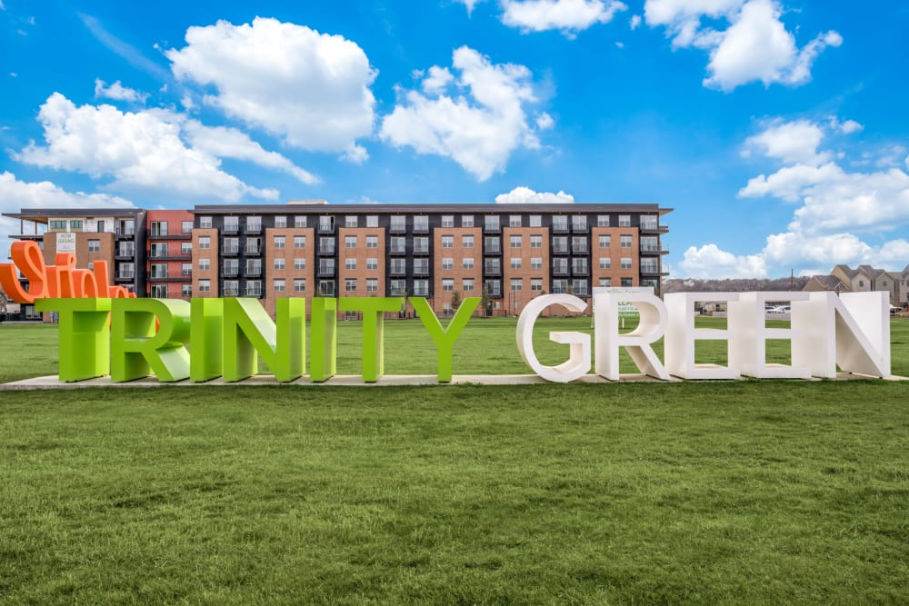 Apartment sign in grassy field at Alta Trinity Green in Dallas, Texas