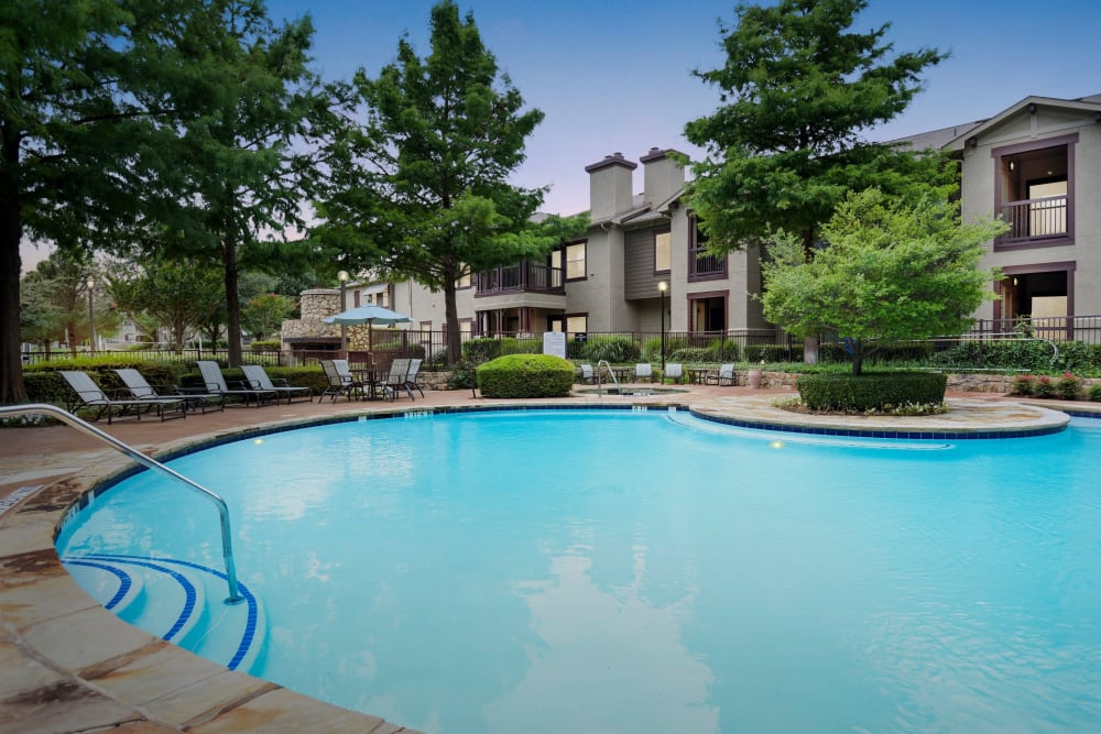 Beautiful pool with a sundeck and a forest backdrop at Ranch ThreeOFive in Arlington, Texas