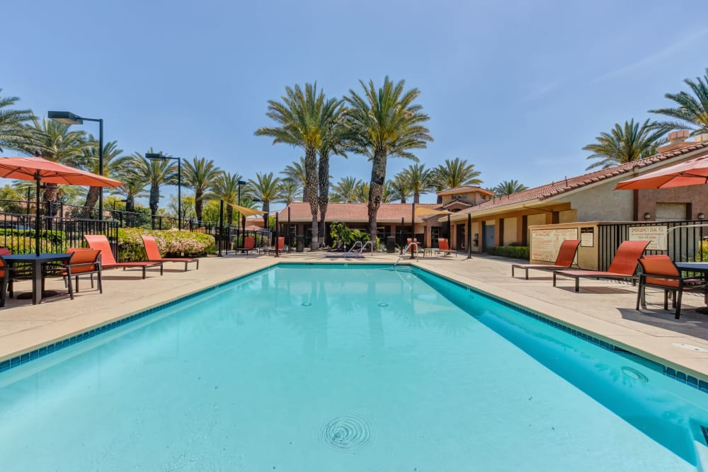 Large swimming pool with a sundeck and lounge chairs at Tuscany Village Apartments in Ontario, California