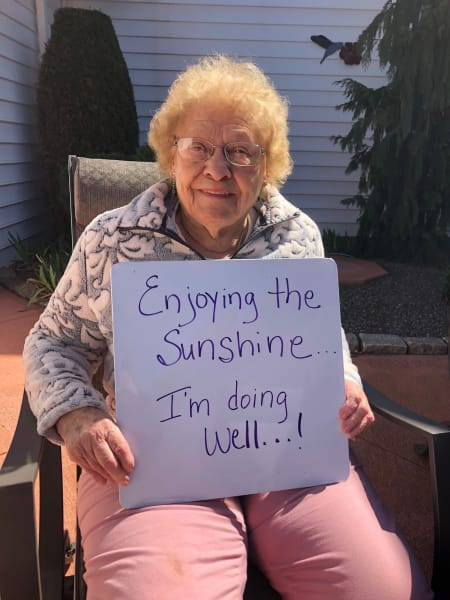 A resident holding up a message at Heritage Senior Living