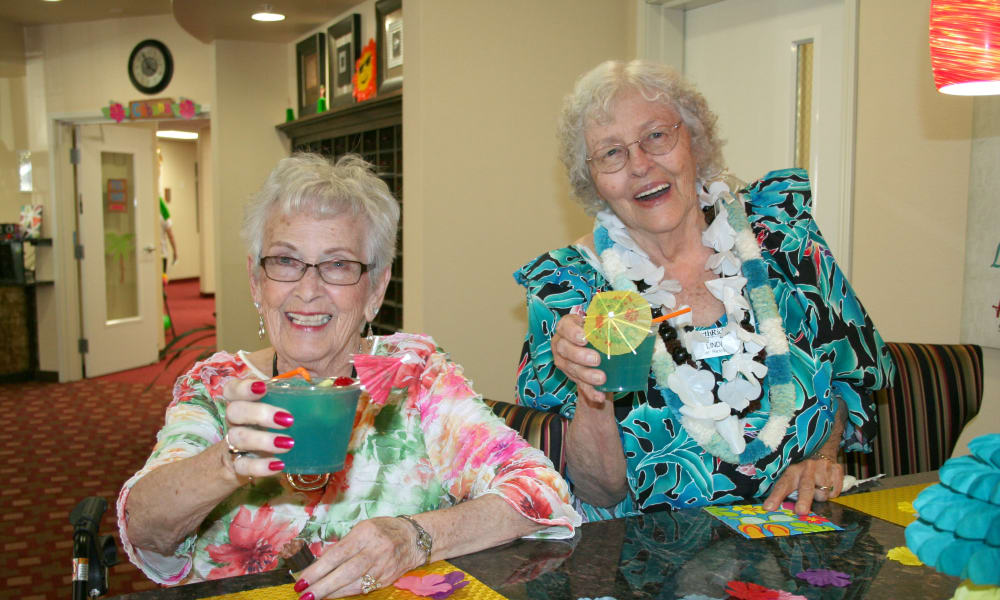 Two happy residents having a drink at Colonial Gardens Gracious Retirement Living in Beverly, Massachusetts