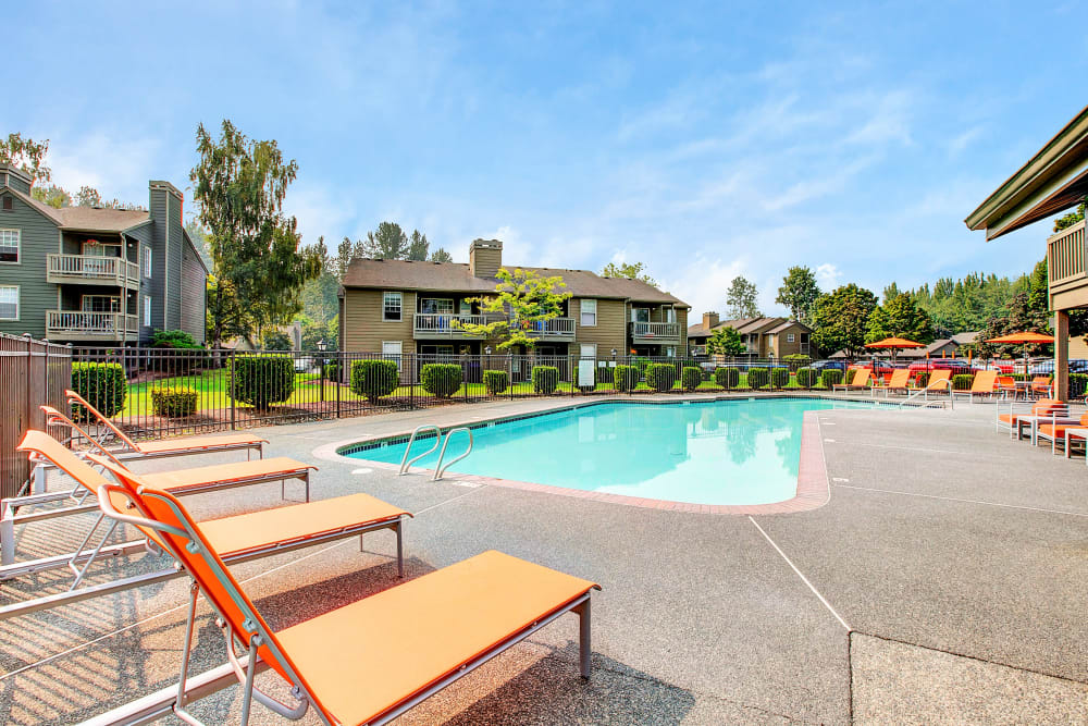 Beautiful resort-style swimming pool with lounge chairs at Waters Edge Apartments in Kent, Washington