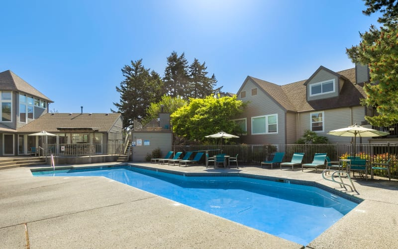 Lounge chairs on the poolside deck at Meadows at Cascade Park Apartments in Vancouver, Washington