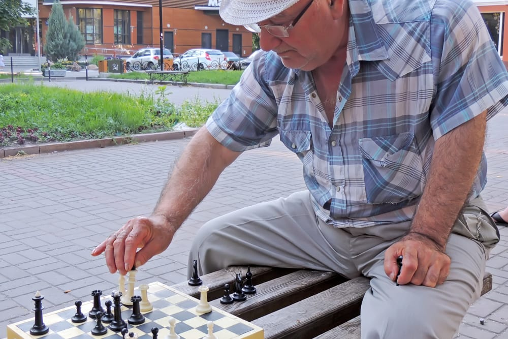 A man playing a game of chess outside at The Iris Senior Living in Great Falls, Montana