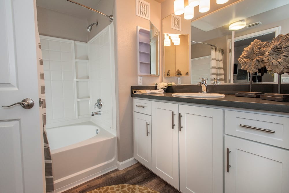 Model bathroom with white cabinetry at Venu at Galleria Condominium Rentals in Roseville, California