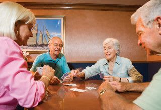 Senior living residents in Discovery Commons play cards together