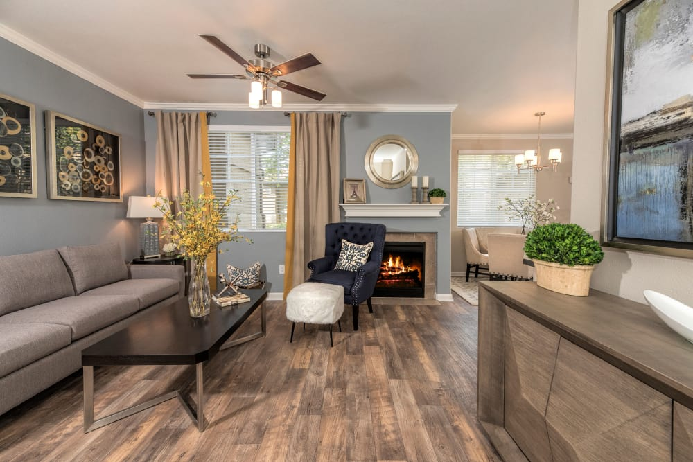 Lovely model living room with faux distressed hardwood flooring at The Artisan Apartment Homes in Sacramento, California