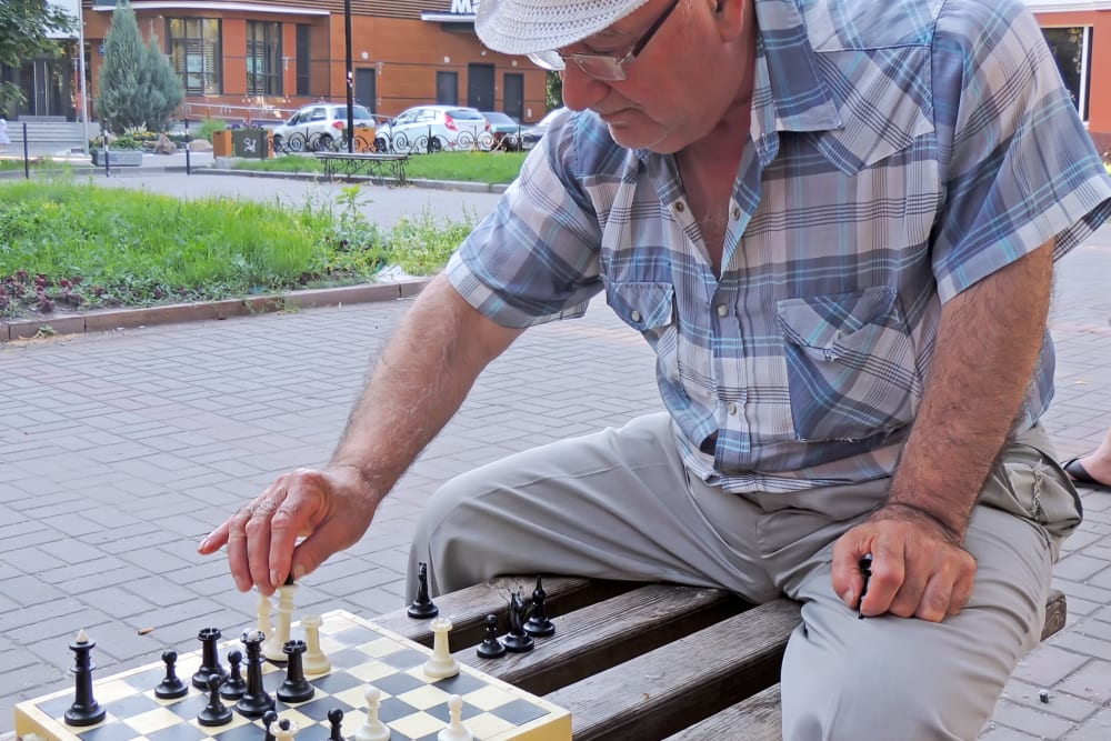 A resident playing chess on a bench near Honeysuckle Senior Living in Hayden, Idaho