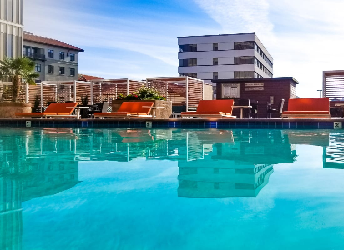 Pool with patio seating at Hillsborough Plaza Apartments in San Mateo, California