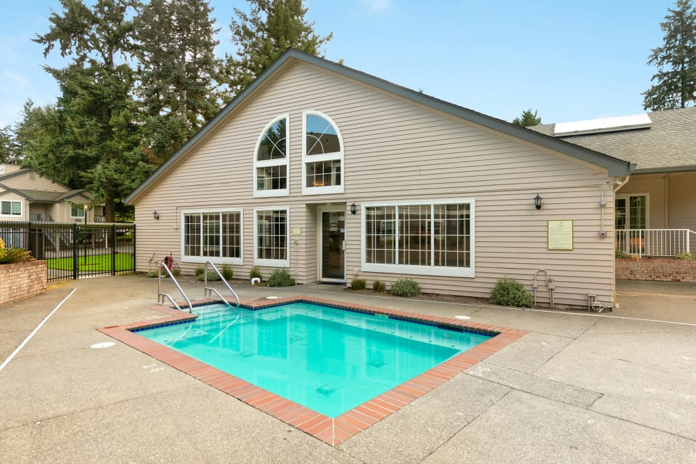 Beautiful bright blue swimming pool with lush trees in the backdrop at Autumn Chase Apartments in Vancouver, Washington