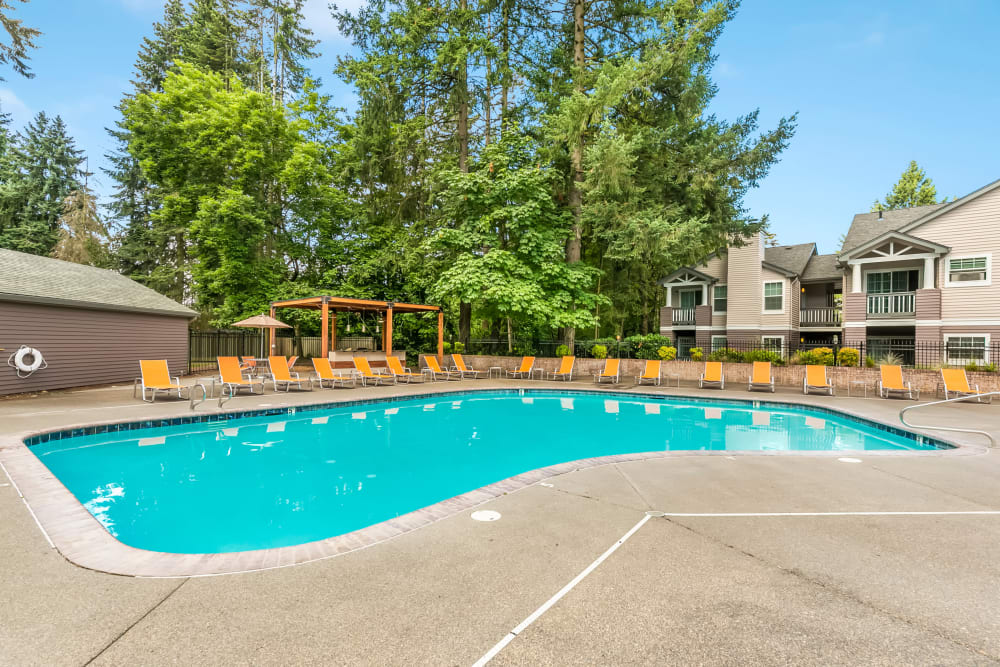 Beautiful blue pool surrounded by orange lounge chairs at Autumn Chase Apartments in Vancouver, Washington