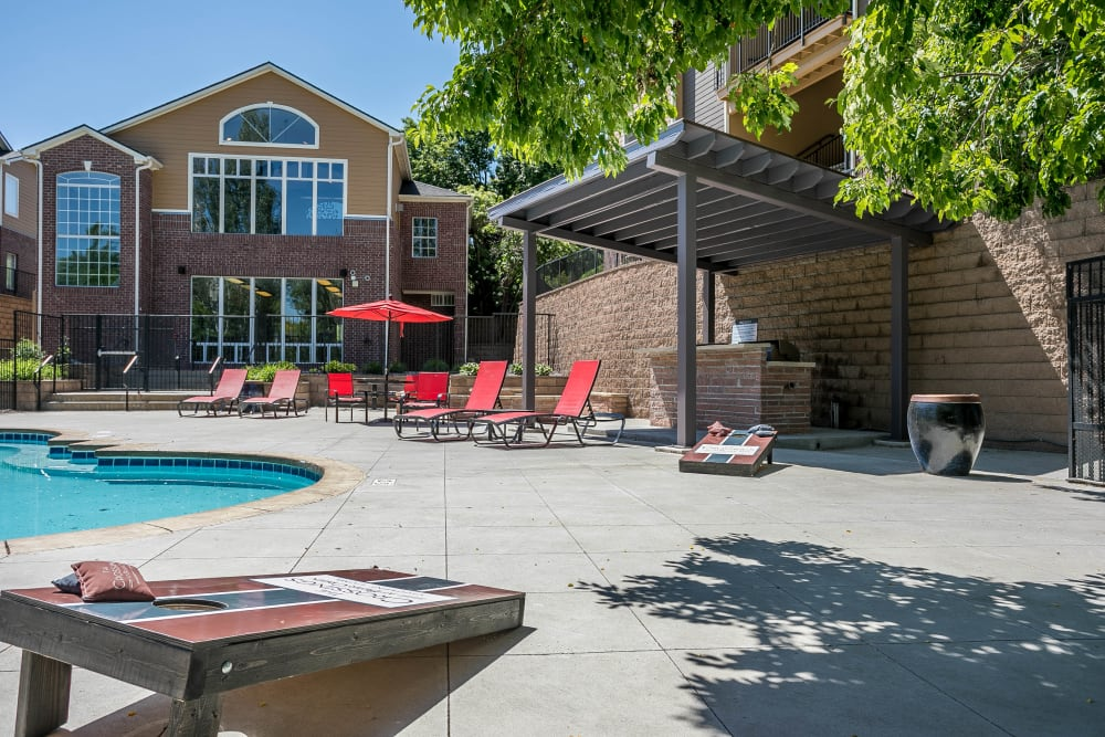 Swimming pool with a sundeck, lounge chairs and corn hole at The Crossings at Bear Creek Apartments in Lakewood, Colorado