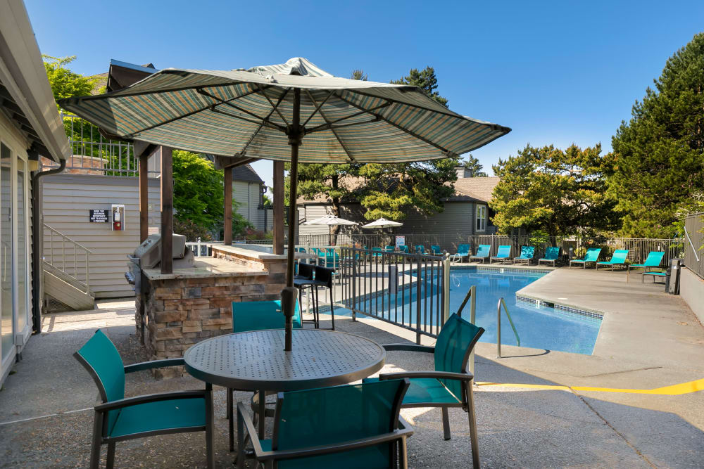 Beautiful resort-style swimming pool with lounge chairs and a barbecue area at Meadows at Cascade Park Apartments in Vancouver, Washington