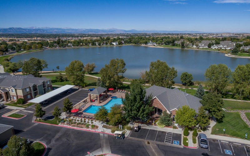 Aerial view of the property and nearby lake at Promenade at Hunter's Glen Apartments in Thornton, Colorado