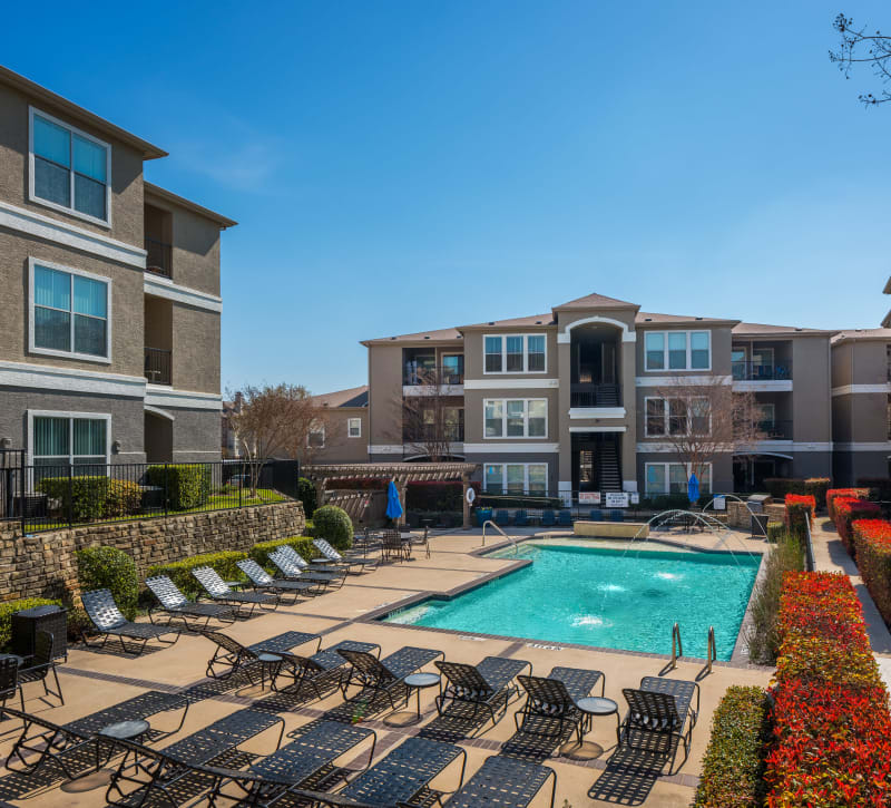 Swimming pool area with fountains and chaise lounge chairs at Vail Quarters in Dallas, Texas