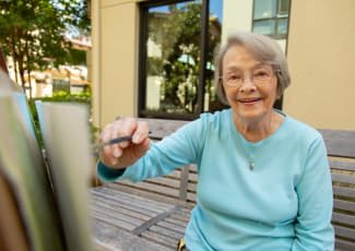 A resident painting outdoors at Summerfield Senior Living in Bradenton, Florida