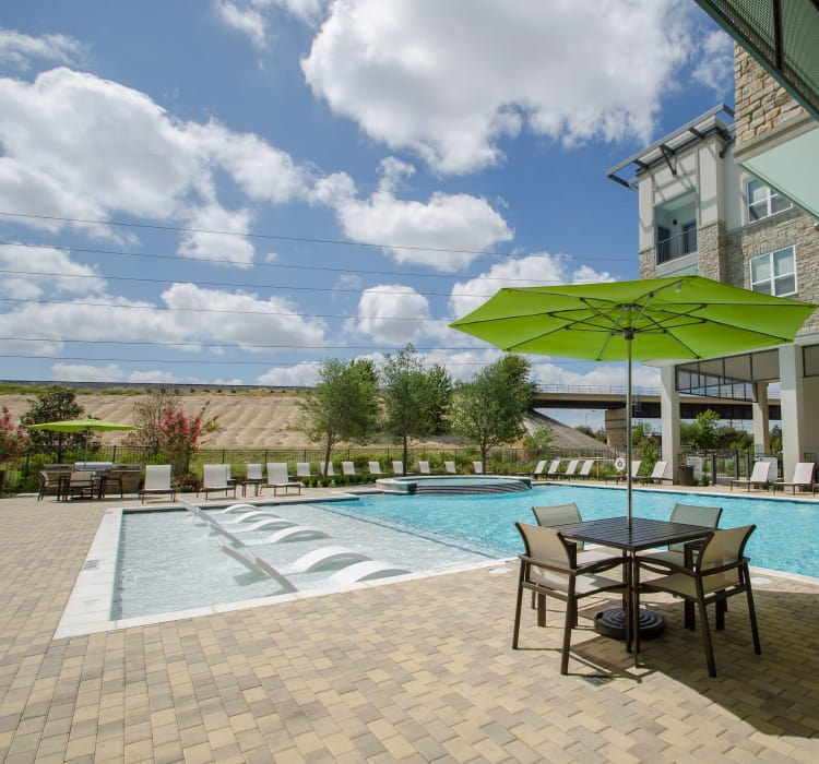 Gorgeously decorated swimming pool area at GreenVue Apartments in Richardson