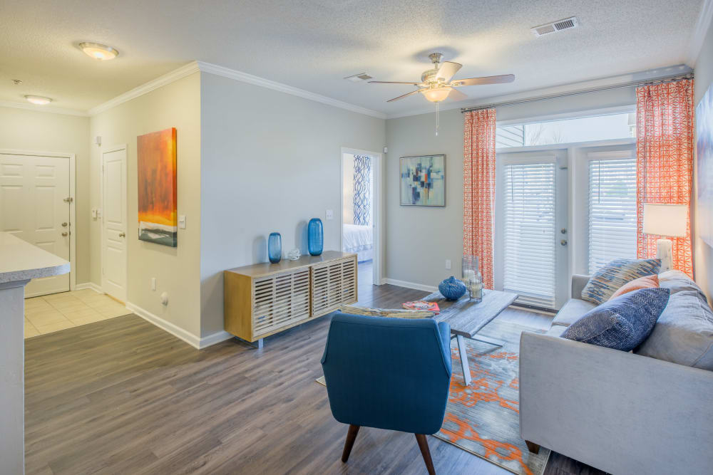 Wood style flooring and modern furnishings in a model home's living area at The Avant at Steele Creek in Charlotte, North Carolina