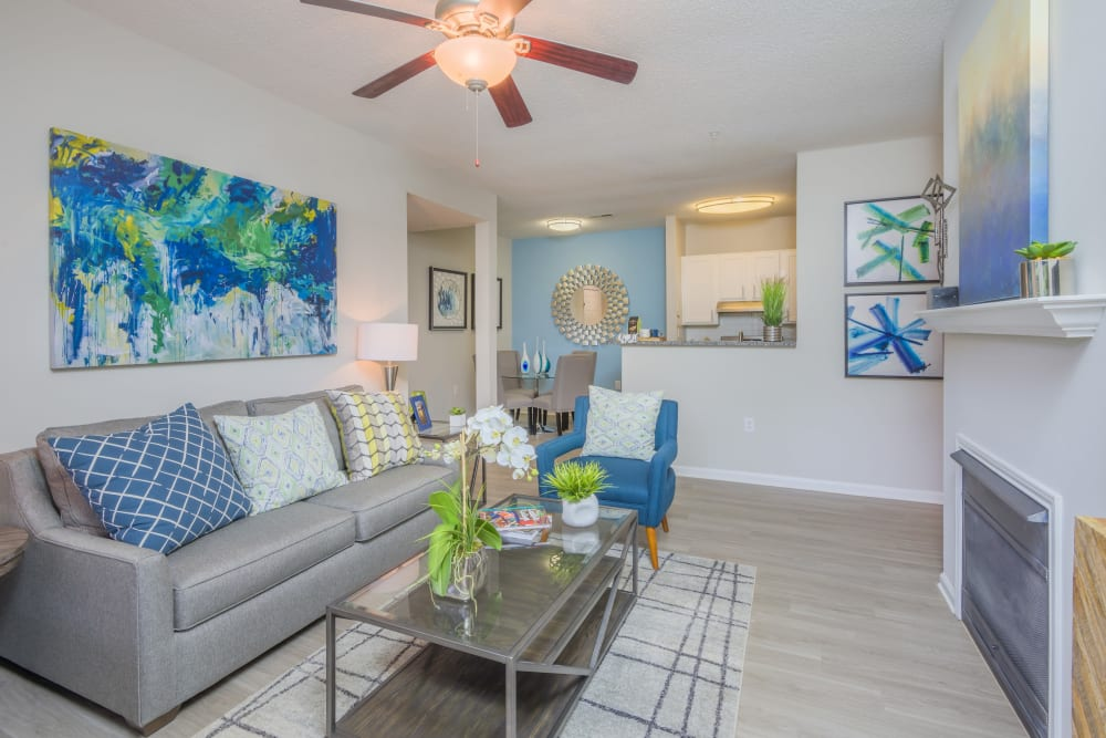 Living room decorated in model home with wood style flooring and a ceiling fan at The Mark in Raleigh, North Carolina