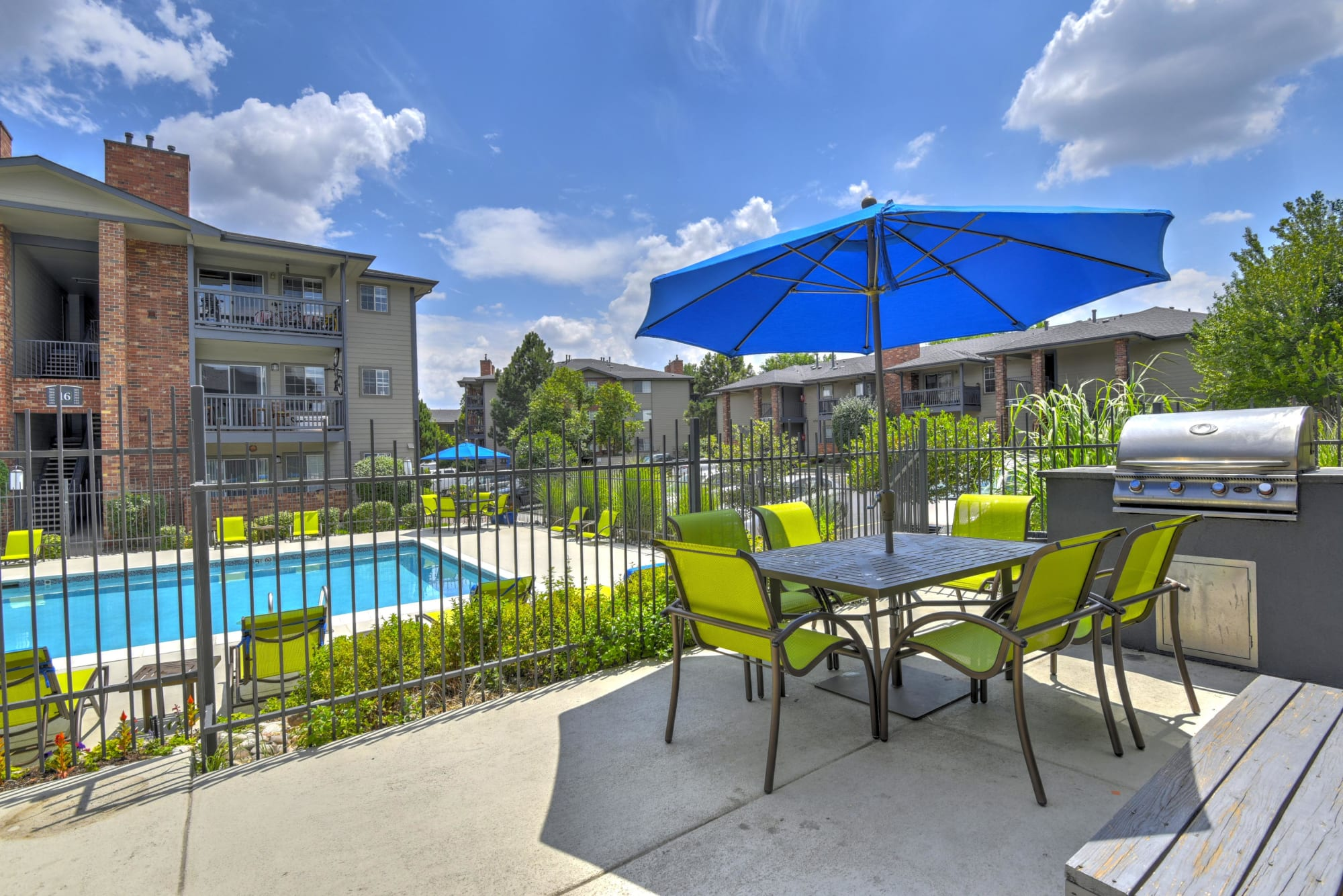 Umbrella covered seating overlooking the pool at Arapahoe Club Apartments in Denver, Colorado