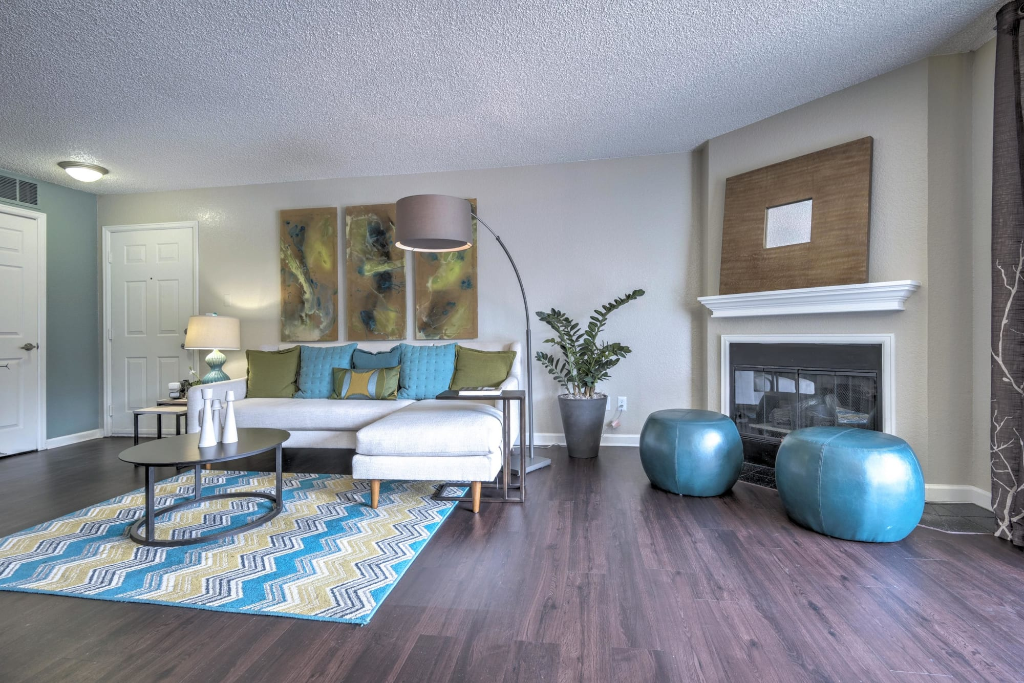 A cozy fireplace in a spacious living room at Arapahoe Club Apartments in Denver, Colorado