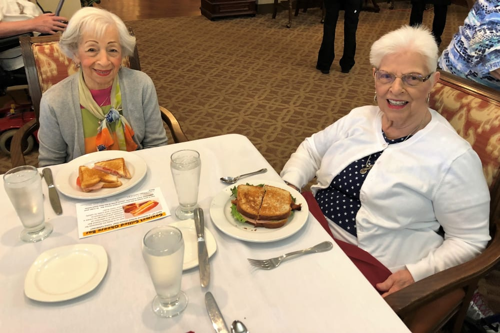 Resident friends having lunch at Merrill Gardens at Solivita Marketplace in Kissimmee, Florida.