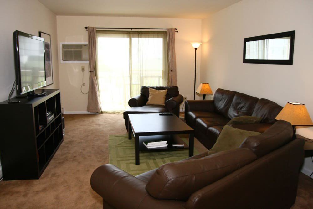 Spacious living room with TV in model home at Terrace Lake Apartments in Bradley Beach, NJ