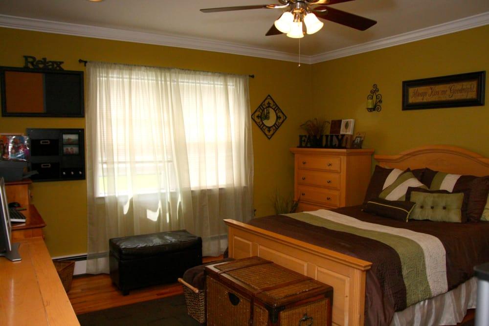 Sun-lit bedroom with ceiling fan at Cedar Village