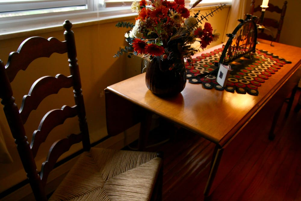 Table with a flower vase and a chair at Haddon Knolls Apartments