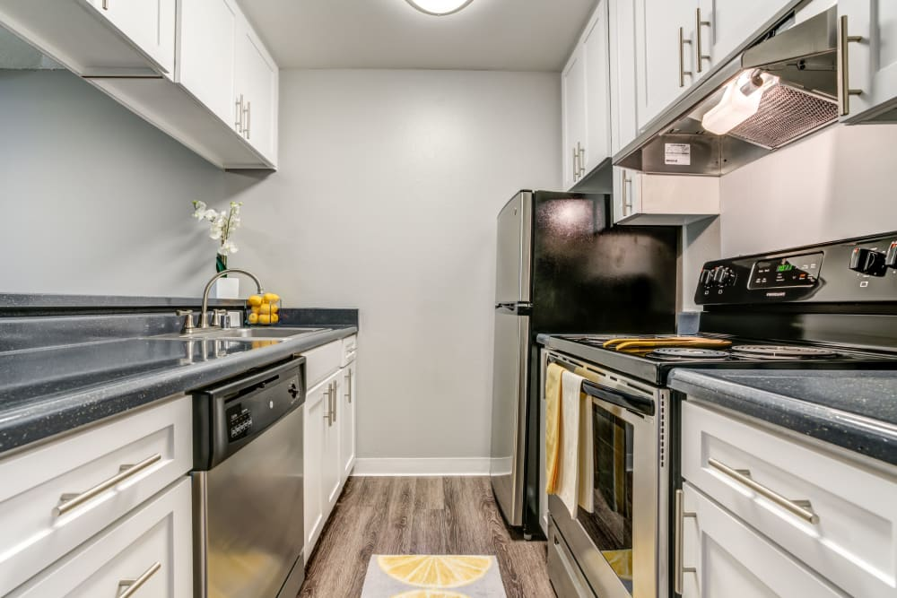 Kitchen with wood-style flooring at The Timbers Apartments in Hayward, California