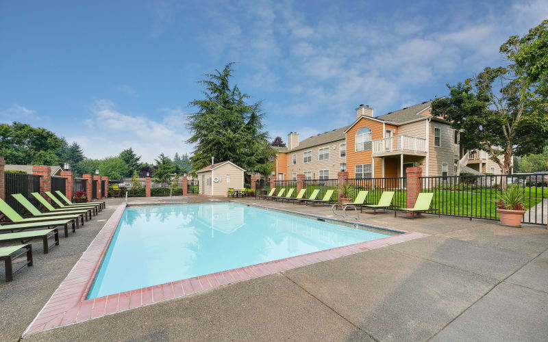 Lounge chairs by the welcoming blue pool on a sunny day at Carriage Park Apartments in Vancouver, Washington