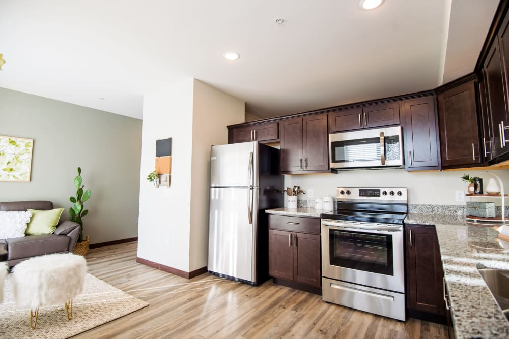 Open kitchen with stainless-steel appliances at Crossroads at Elm Creek in Maple Grove, Minnesota