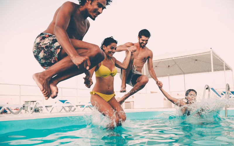 Residents jumping into the pool at Willow Oaks Apartments in Bryan, Texas