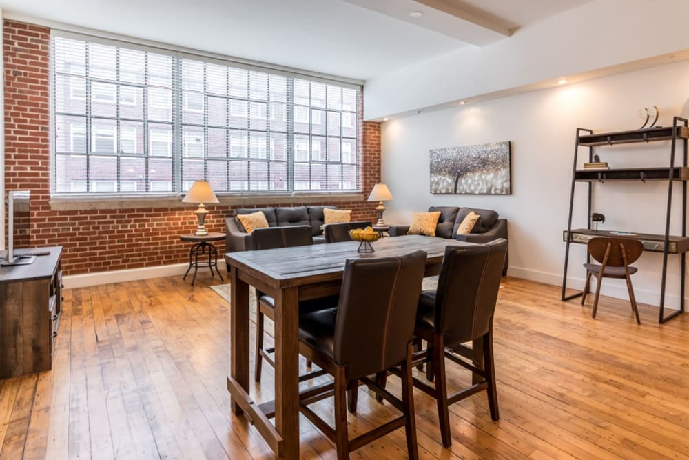 Model living and dining area with large windows at The Gallery Lofts in Winston Salem, North Carolina