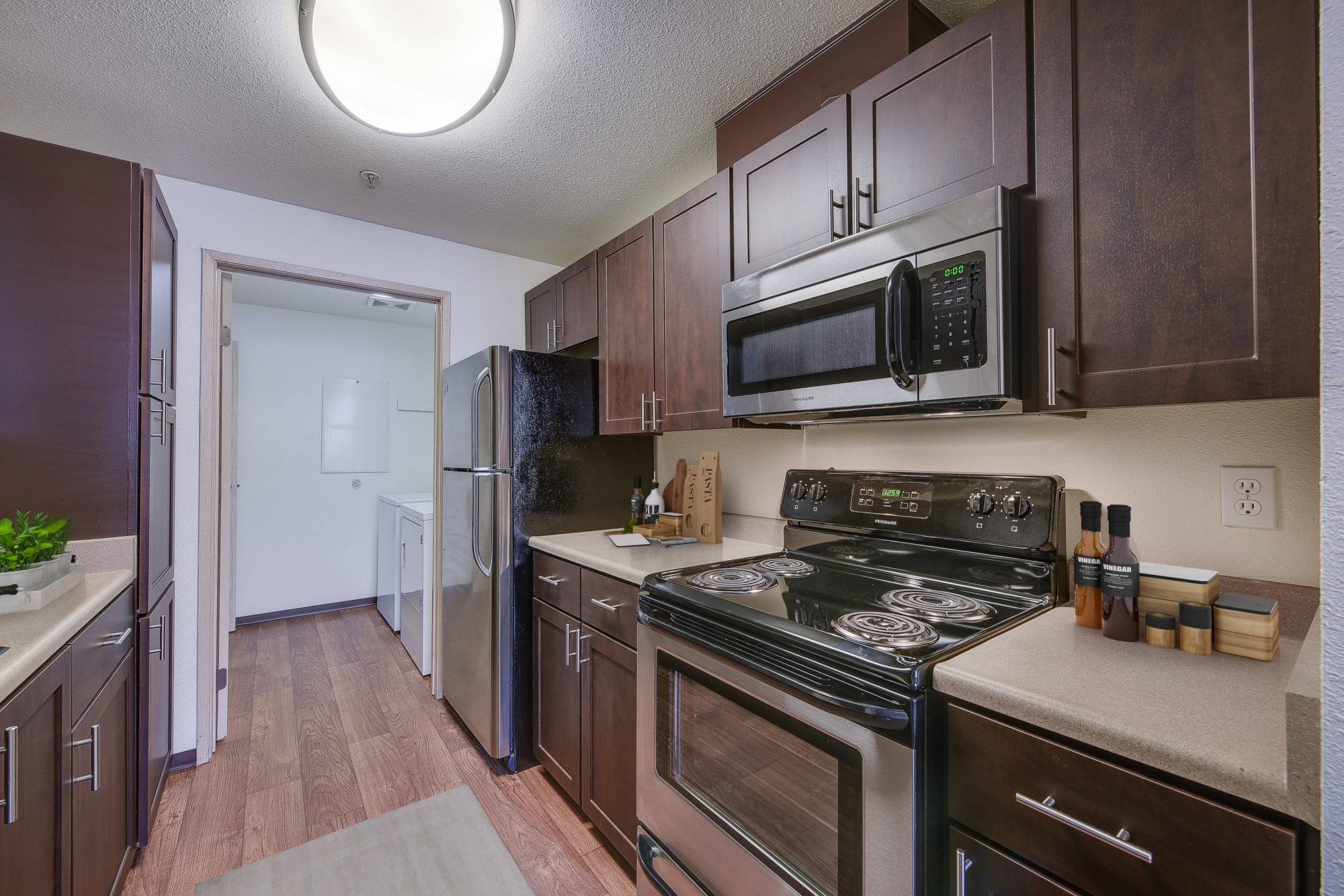 Brown cabinets in a renovated kitchen with stainless steel appliances at Renaissance at 29th Apartments in Vancouver, Washington