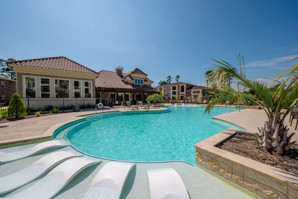 Outdoor pool with lounge chairs at Hilltops in Conroe, Texas